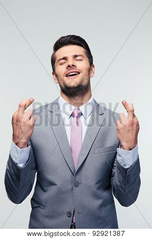 Handsome businessman with fingers crossed over gray background