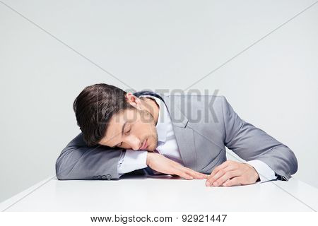 Businessman sleeping on the table over gray background