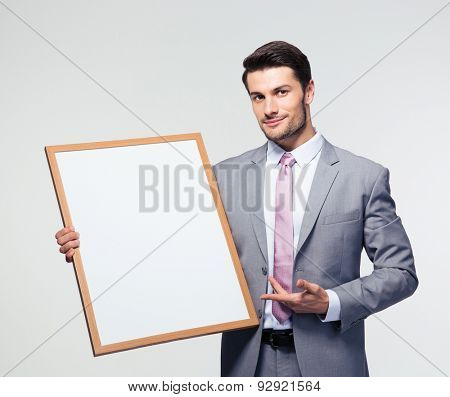 Happy businessman presenting blank board over gray background. Looking at camera