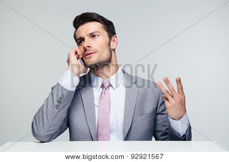 Pensive businessman sitting at the table and talking on the phone over gray background. Looking away