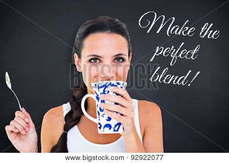 Pretty brunette having cup of tea against black background