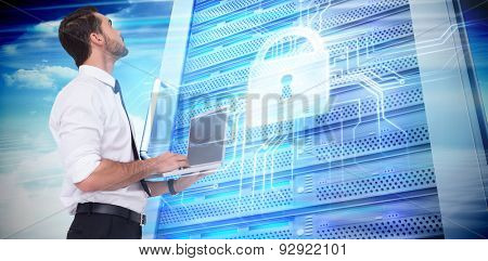 Sophisticated businessman standing using a laptop against composite image of server tower