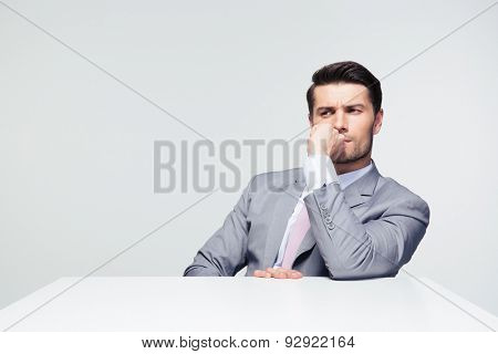 Thoughtful businessman sitting at the table over gray background and looking away
