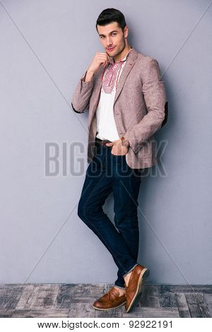 Full length portrait of a fashion man standing over gray background