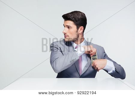 Businessman sitting at the table and putting money in pocket over gray background. Looking away