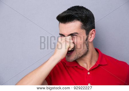 Casual man covering his nose with hand over gray background