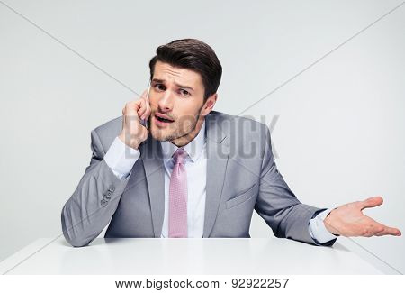Handsome businessman sitting at the table and talking on the phone over gray background