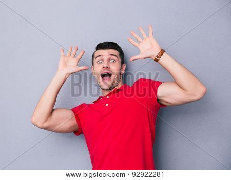 Portrait of a scared casual man over gray background