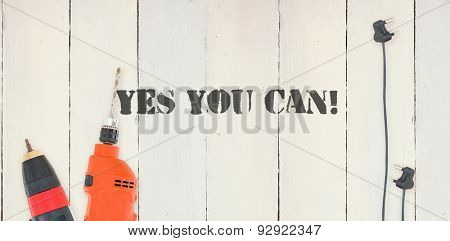 The word yes you can! against diy tools on wooden background