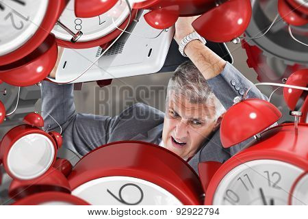 Angry businessman breaking laptop against grey background with vignette