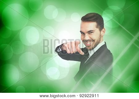 Happy businessman pointing his finger against green abstract light spot design