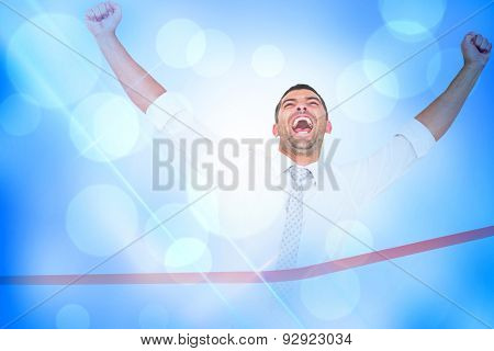 Businessman crossing the finish line against blue abstract light spot design