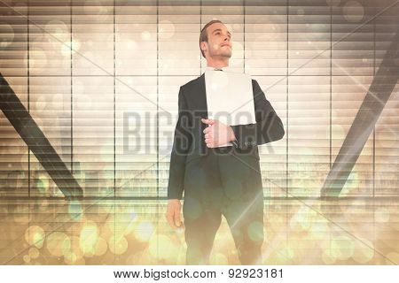 Businessman looking up holding laptop against window overlooking city