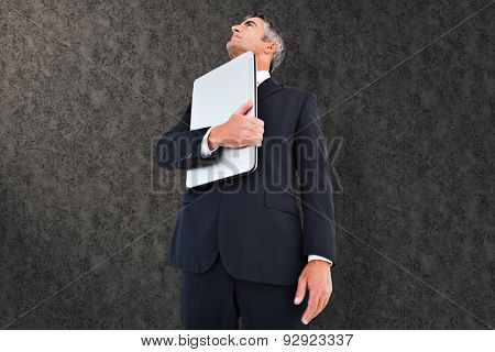 Businessman in suit holding his laptop proudly against grey background