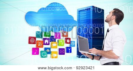 Sophisticated businessman standing using a laptop against composite image of cloud with apps