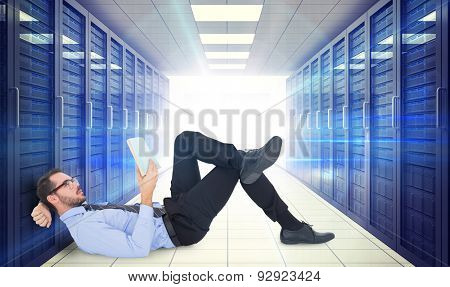 Businessman lying on the floor while reading a book against digitally generated server room with towers