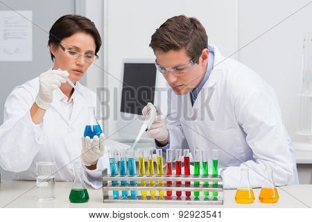 Scientists working attentively with test tube in laboratory