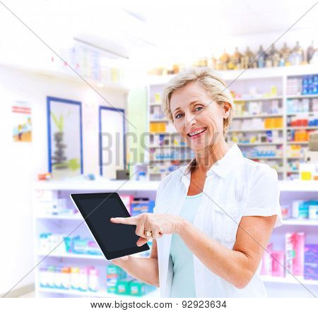 Happy mature woman pointing to tablet pc against close up of shelves of drugs