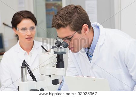 Scientists looking attentively in microscope in laboratory