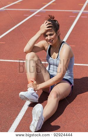 Runner with ankle injury sitting on track
