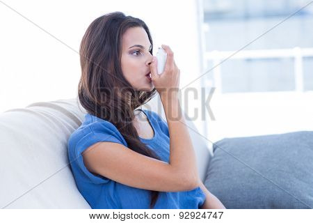 Beautiful brunette using inhaler in the living room