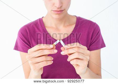 Pretty woman breaking a cigarette on white background