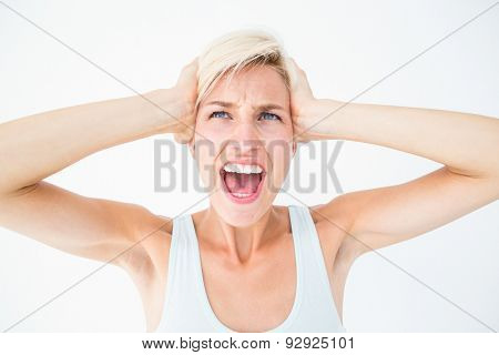 Angry blonde screaming and holding her head on white background