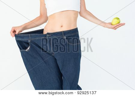 Slim woman wearing too big jeans holding an apple on white background