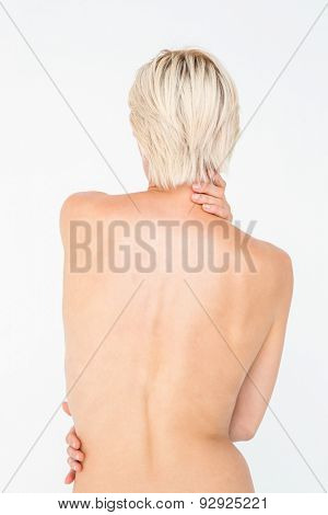 Beautiful topless woman touching her back on white background