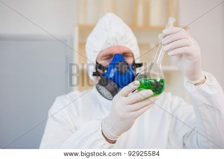 Scientist in protective suit examining green precipitate in the laboratory