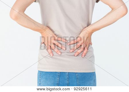 Woman having a back ache and holding her back on white background