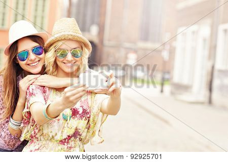 A picture of two happy girl friends taking selfie in the city