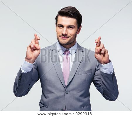 Happy businessman with fingers crossed over gray background. Looking at camera