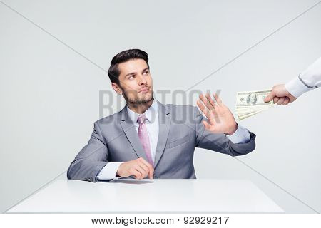 Businessman sitting at the table and gesturing stop sign while someone proposing money to him over gray background