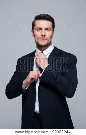 Confident businessman straightening his tie over gray background and looking at camera