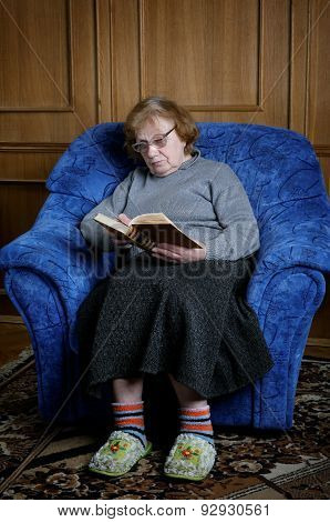 The Old Woman Sits In An Armchair And Reads The Book