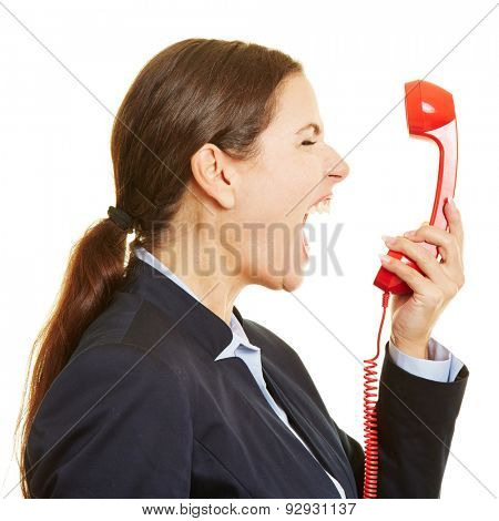 Angry businesswoman screaming loudly into a red phone