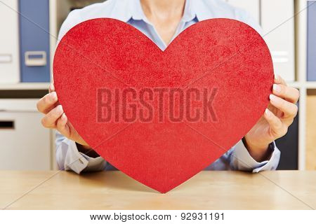 Hands of a woman holding big red heart on a desk