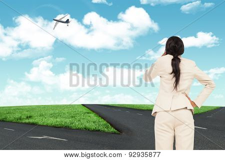 Thinking businesswoman against road leading out to the horizon