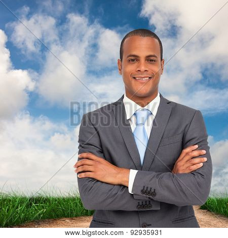 Charismatic young businessman with arms crossed against road leading out to the horizon