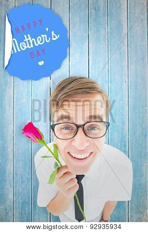 Geeky hipster holding a red rose against wooden planks