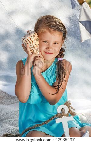 Little Girl Listens To The Sea Through The Shell