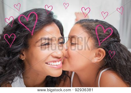 Red Hearts against pretty woman lying on bed with her daughter kissing cheek