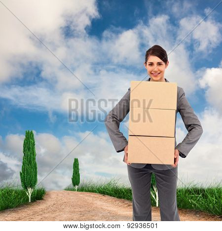 Smiling businesswoman carrying cardboard boxes against road leading out to the horizon