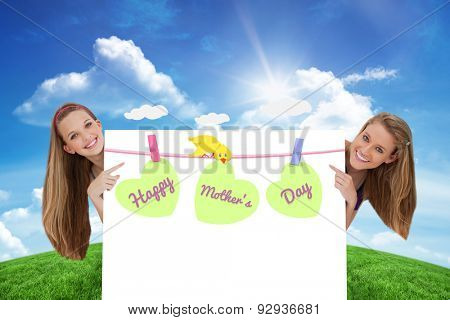 Portrait of wo long hair women back of a blank sign against green hill under blue sky