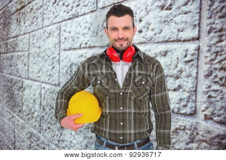 Handyman with earmuffs holding helmet against grey brick wall