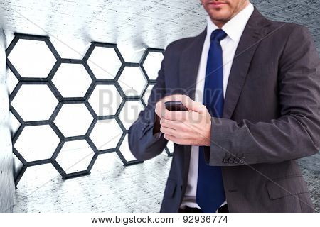 Focused businessman texting on his mobile phone against hexagon room