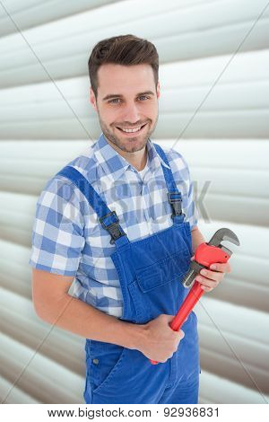 Confident young male repairman holding monkey wrench against grey shutters