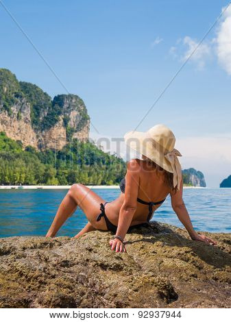 Summer vacation in Thailand woman on the beach in beach hat enjoying summer holidays looking at the ocean