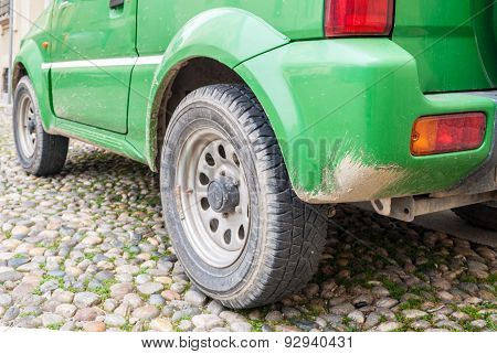 Green automobile with mud